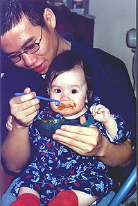 Uncle James feeding Janis solids for the first time!  (Carrots) - February 2000
